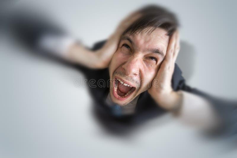De jonge schizofrene mens lijdt aan hoofdpijn en het behandelen van zijn oren met handen royalty-vrije stock afbeeldingen
