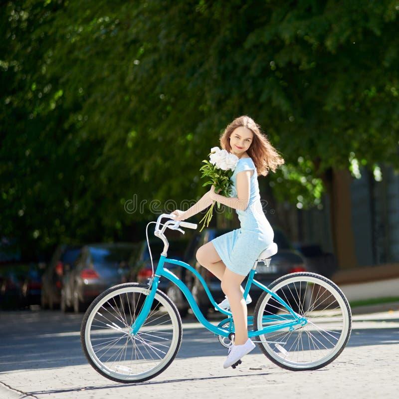 De jonge schoonheid op uitstekende fiets speldde haar pioenen, zonnige dag stock afbeeldingen
