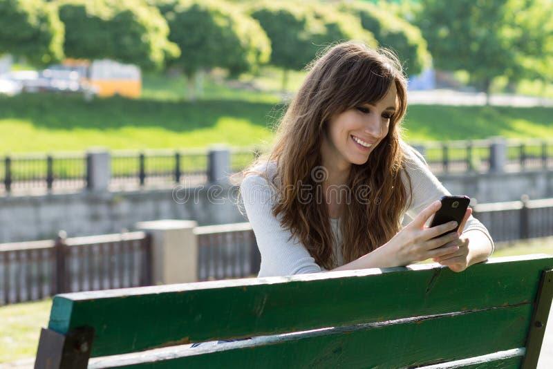 De jonge schoonheidsvrouw heeft pret met het gebruiken van smartphone royalty-vrije stock foto's