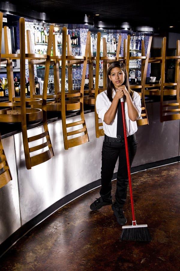 De jonge schoonmaken van de restaurantarbeider stock afbeeldingen