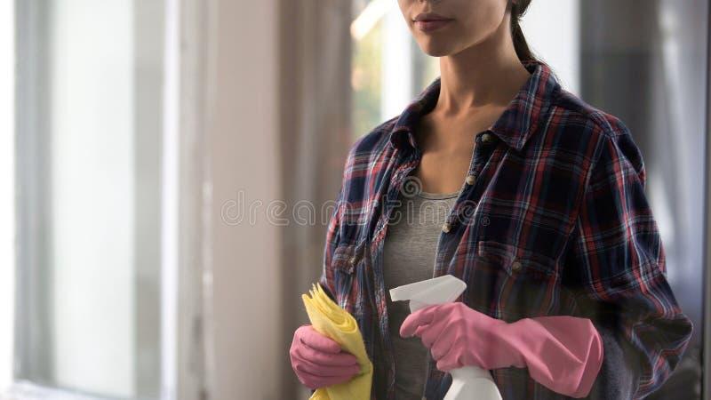 De jonge schoonmakende hulpmiddelen van de vrouwenholding in handen, atmosfeer versheid en comfort royalty-vrije stock afbeeldingen