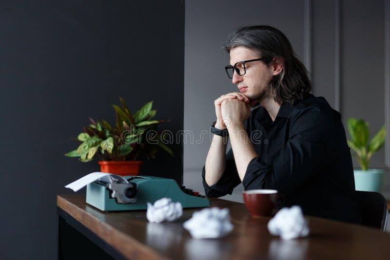 De jonge schrijver in geen meditatie, heeft inspiratie, gezet bij lijst, dichtbij schrijfmachine Het ontspruiten in studio royalty-vrije stock fotografie