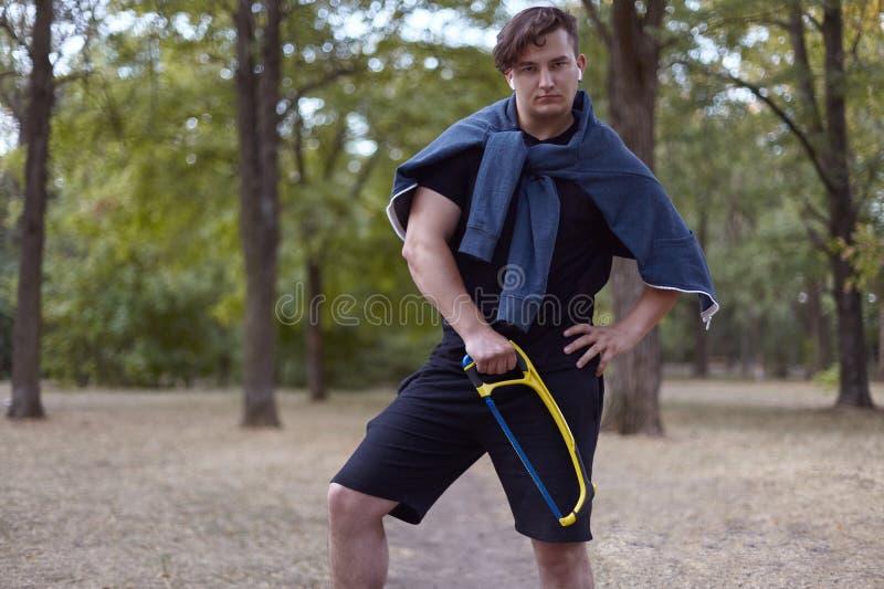 De jonge sexy mens bevindt zich met handzaag in de bos vrijetijdskleding, witte oortelefoons In openlucht, exemplaarruimte Humeur stock afbeelding
