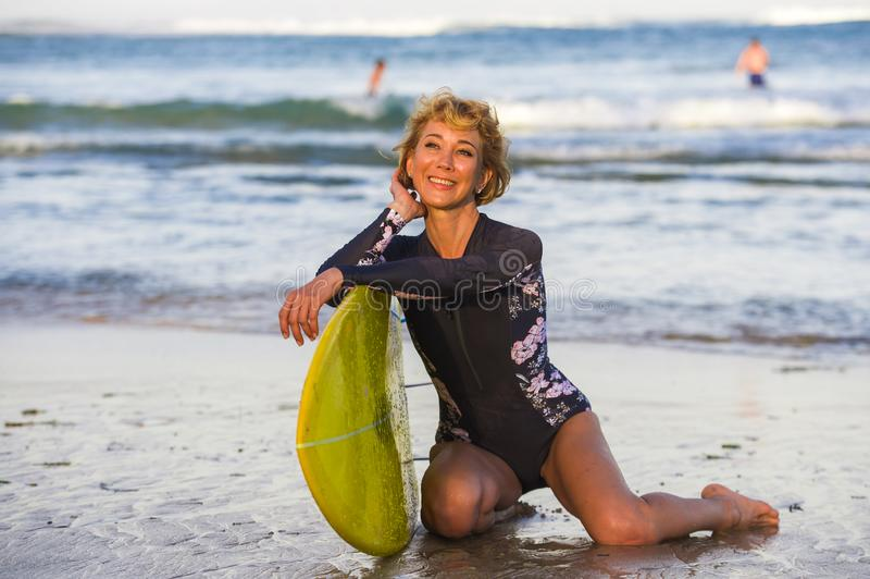 De jonge sexy mooie en gelukkige zitting die van de surfervrouw op strandzand gele brandingsraad houden die de vrolijke het genie stock afbeelding