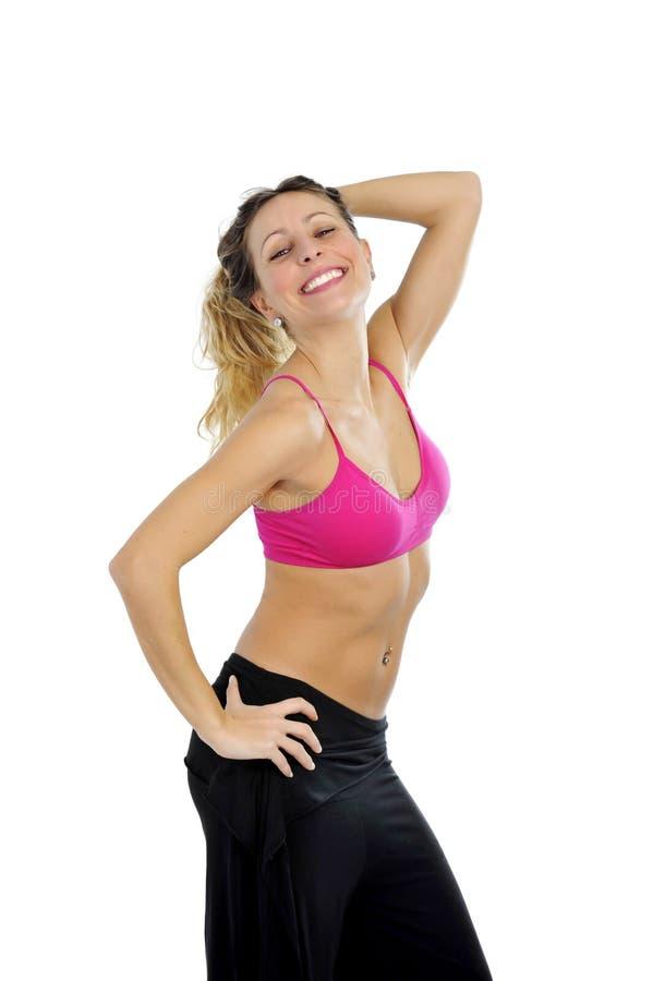 De jonge sexy mooie vrouw in sport kleedt stellen verleidelijk met hoogste bustehouder in fitness concept stock foto