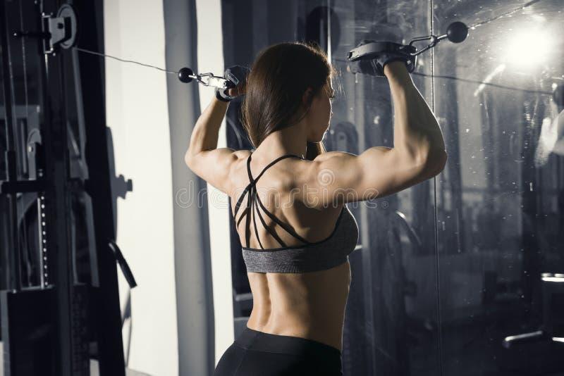 De jonge sexy training van de geschiktheidsvrouw met opleidingsmachine in de gymnastiek stock foto