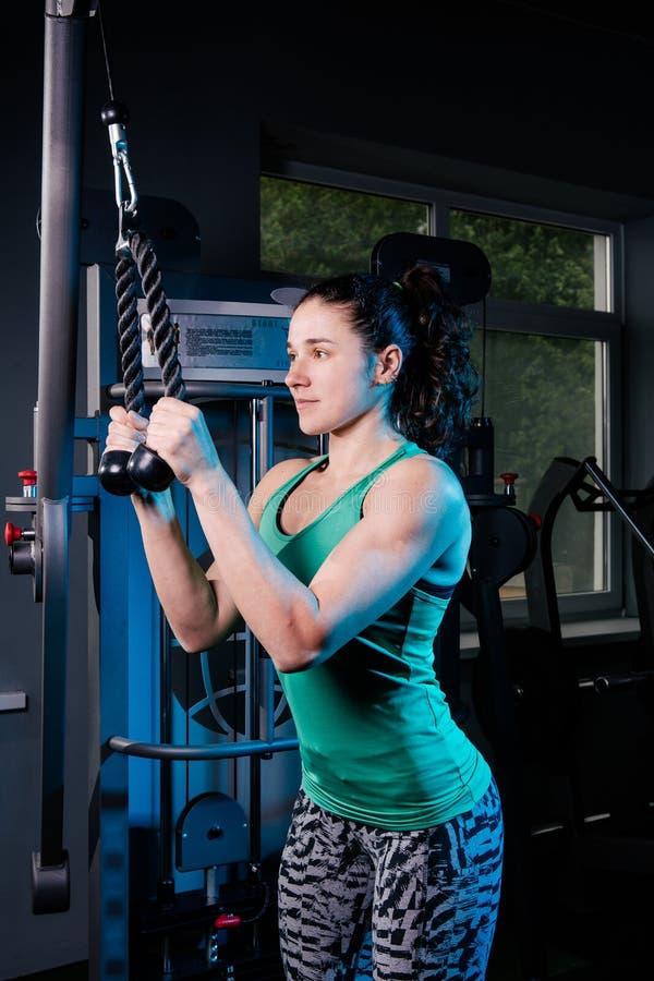 De jonge sexy training van de geschiktheidsvrouw met opleidingsmachine in de gymnastiek royalty-vrije stock afbeelding