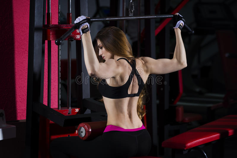De jonge sexy training van de geschiktheidsvrouw met opleidingsmachine in de gymnastiek royalty-vrije stock foto's