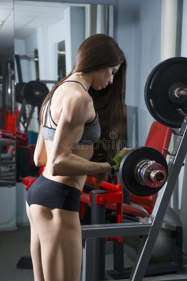 De jonge sexy training van het geschiktheidsmeisje met barbell in de gymnastiek , vrouw in sportslijtage met perfect spierlichaam royalty-vrije stock afbeelding