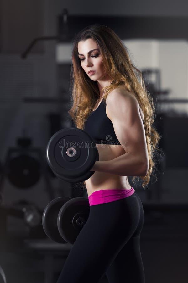 De jonge sexy training van het geschiktheidsmeisje met domoren in de gymnastiek, vrouw met perfect spierlichaam royalty-vrije stock foto