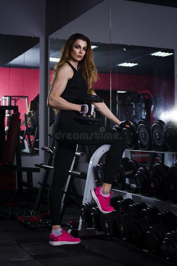 De jonge sexy training van het geschiktheidsmeisje met domoren in de gymnastiek, vrouw met perfect spierlichaam royalty-vrije stock afbeeldingen
