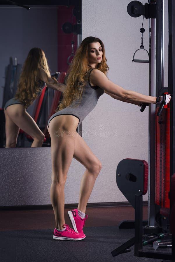 De jonge sexy training van het geschiktheidsmeisje met trainer in de gymnastiek, vrouw met perfect spierlichaam royalty-vrije stock foto