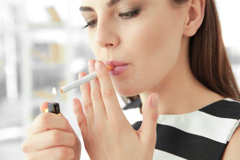 De jonge Sigaret van de Vrouwenverlichting stock fotografie