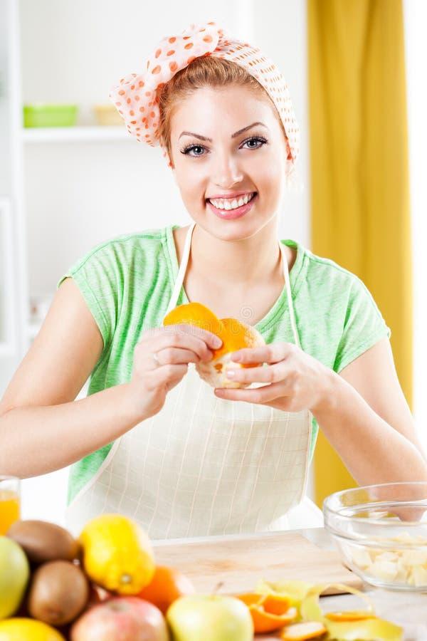 De jonge sinaasappelen van de vrouwenschil. stock afbeeldingen