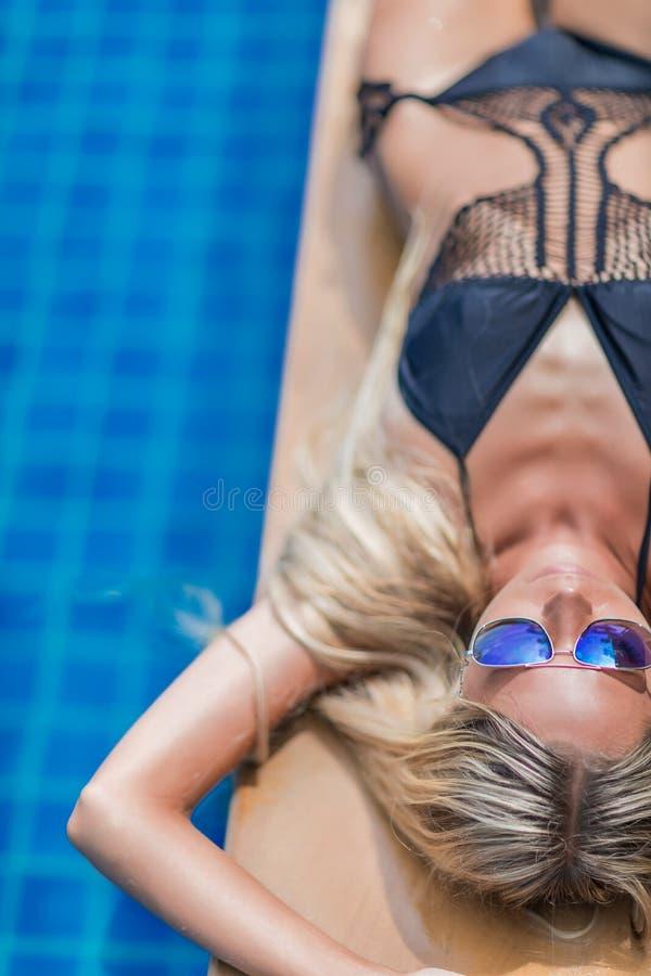 De jonge slanke blondevrouw met lang haar in zonnebril krijgt bruine kleur royalty-vrije stock foto