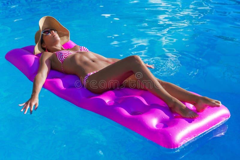 De jonge slanke donkerbruine vrouw in strohoed krijgt bruine kleur op een luchtmat stock fotografie