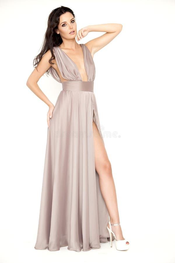De jonge slanke sexy vrouw in bruine kleding isolaten op witte backgroun royalty-vrije stock afbeeldingen