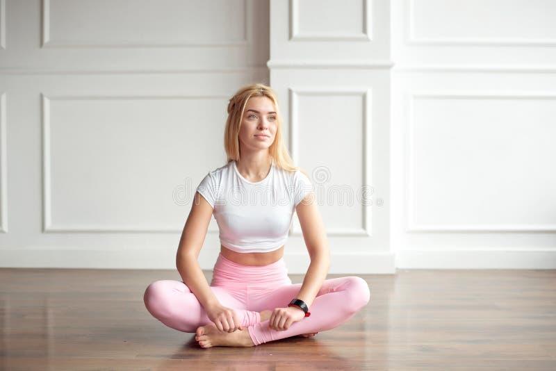 De jonge slanke vrouw met een atletisch lichaam met lang blond haar, gekleed in witte sportkleding en roze beenkappen, zit op stock afbeeldingen