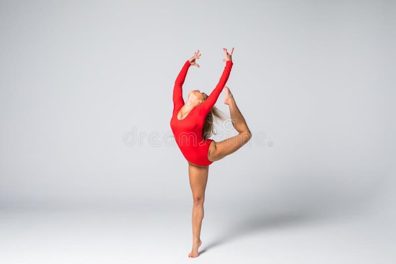 De jonge slanke vrouw van het schoonheidsblonde in rood lichaam die en gymnastiek- oefeningen op witte achtergrond springen doen stock fotografie