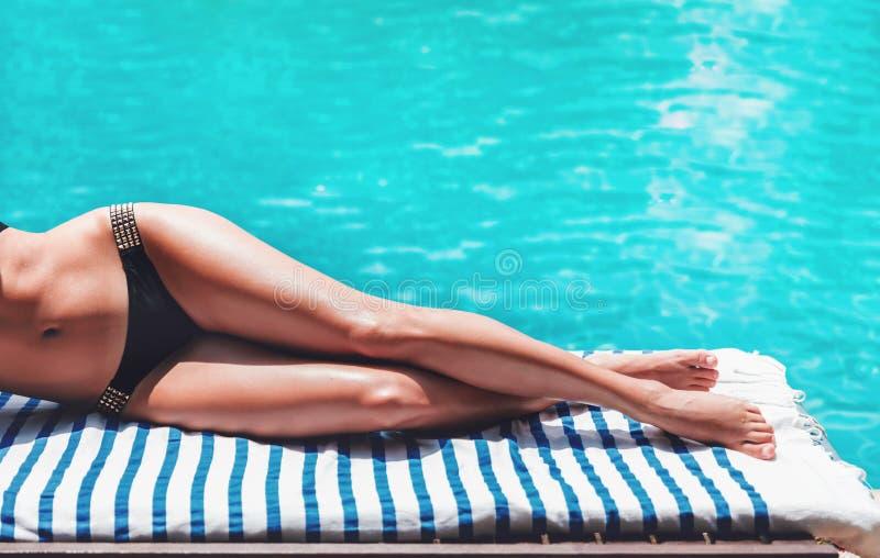 De jonge slanke vrouwenbenen in bikini ontspannen dichtbij zwembad in zonlanterfanter royalty-vrije stock fotografie