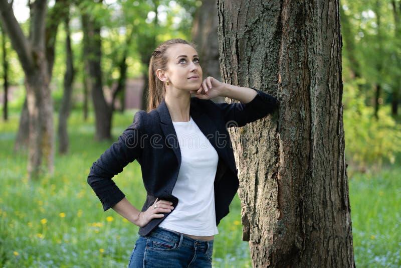 De jonge slanke vrouwenrust op een boomboomstam, op haar gezicht is een dromerige uitdrukking royalty-vrije stock afbeeldingen