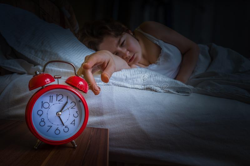 De jonge slaperige vrouw is ontwaken bij ochtend en zet wekker uit royalty-vrije stock afbeeldingen