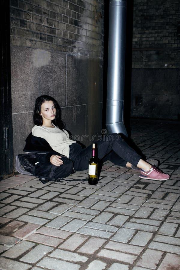 De jonge slechte zitting van het ttenagemeisje bij vuile muur op vloer met fles van wijnstok, slechte vluchtelings alcoholische,  stock foto's