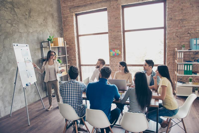 De jonge slimme dame in glazen rapporteert aan het team van collega's over het nieuwe project op de vergadering met de witte raad stock foto's