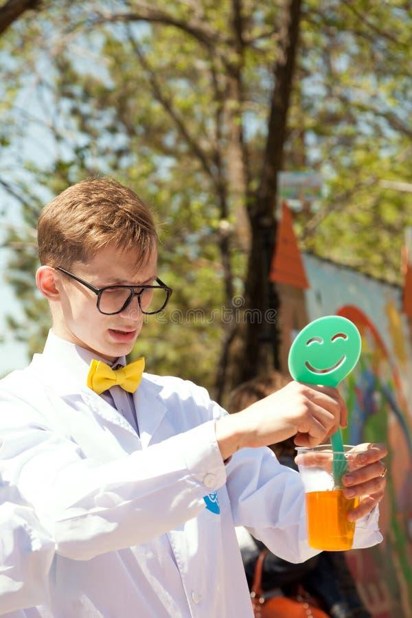 De jonge slimme professor die een experiment uitvoeren bij wetenschap toont voor jonge geitjes stock afbeeldingen