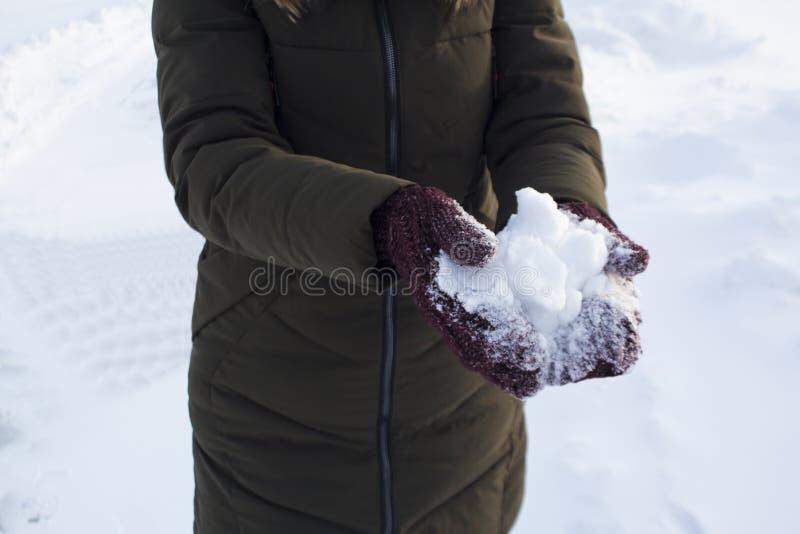 De jonge sneeuw van de vrouwenholding in haar dient vuisthandschoenen, de winter, pret, vreugde, sporten, recreatie, kinderen in stock afbeeldingen