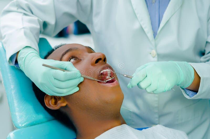 De jonge Spaanse mens die als voorzitter liggen die tandbehandeling met open mond ontvangen, tandartshanden het dragen gloves het royalty-vrije stock foto's