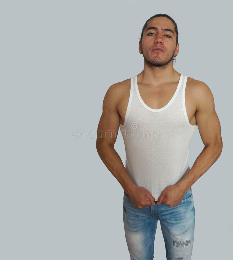 De jonge Spaanse mens met haar verbond gedaan in witte t-shirt sleeveless, met zijn handen uitgestrekte t-shirt royalty-vrije stock afbeeldingen