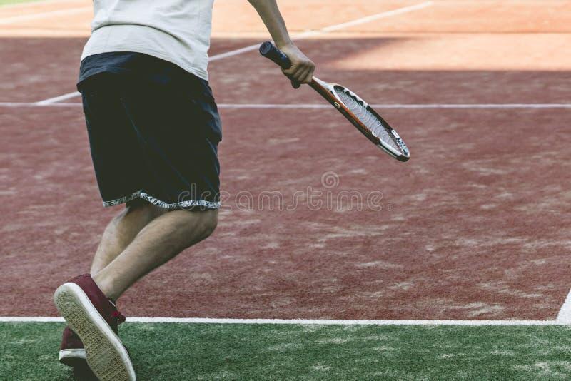 De jonge speler van het sport mannelijke tennis op de praktijk van het de zomerkamp stock foto