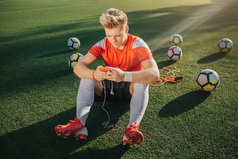 De jonge speler zit alleen op groen gazon Hij heeft rust de telefoon van de Kerelgreep in handen met hoofdtelefoons Zes ballen zi royalty-vrije stock fotografie