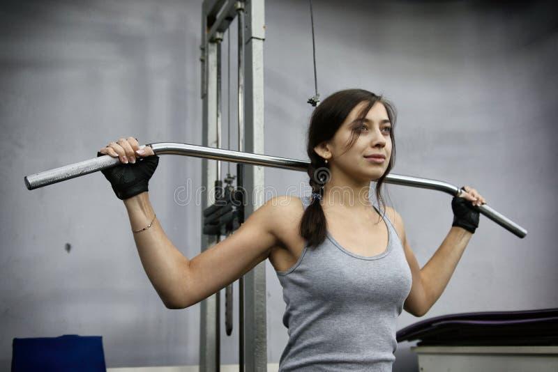 De jonge spieren van de vrouwenverbuiging op de machine van de kabelgymnastiek royalty-vrije stock afbeelding