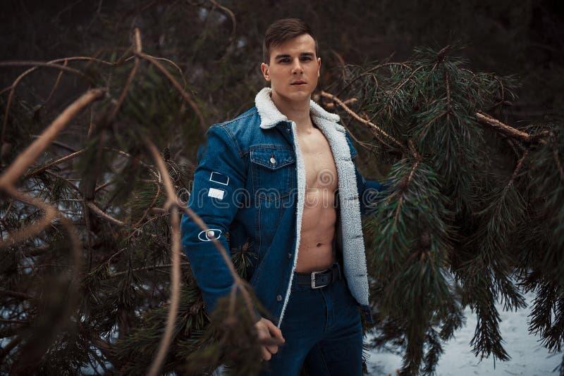 De jonge spiermens in losgeknoopt jasje met blote borst bevindt zich naast pijnboomboom in de winterbos royalty-vrije stock afbeelding