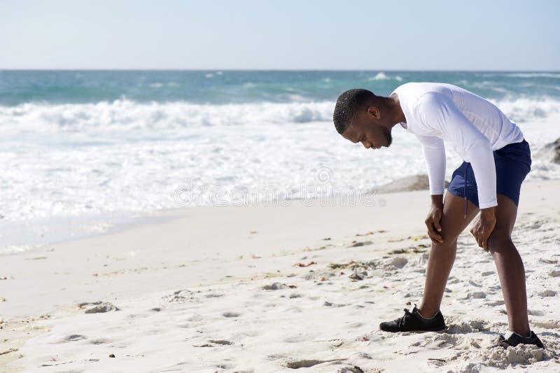 De jonge sportenmens uitgeput na werkt met handen op knieën uit royalty-vrije stock foto's