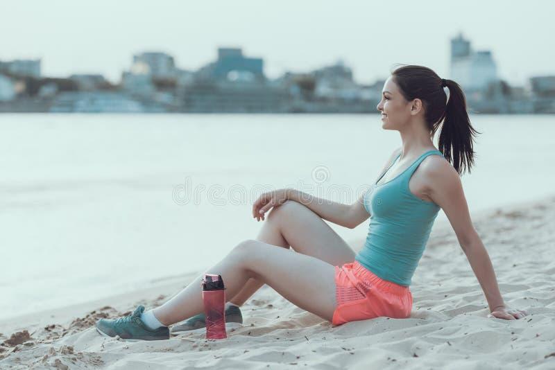 De jonge sportenvrouw rust na het lopen op strand stock afbeelding