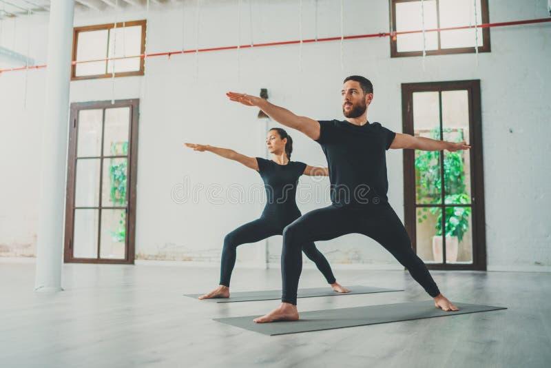 De jonge sportieve man en de vrouw oefenen yogaoefeningen in de studio uit Paar van jonge sportieve mensen die yoga uitoefenen stock fotografie