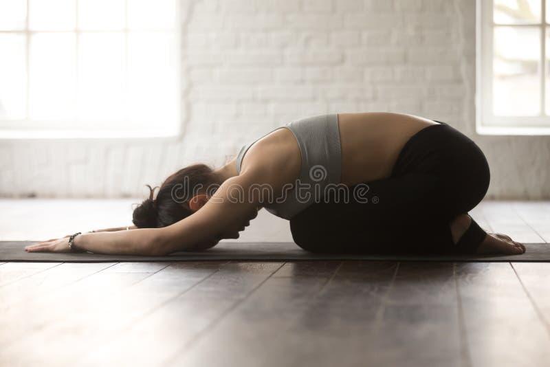 De jonge sportieve vrouw in Balasana stelt, witte zolderstudio backgroun stock foto