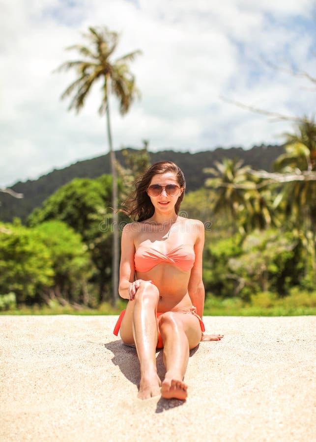 De jonge sportieve vrouw in oranje bikini en zonnebril zit op fijn strandzand, wind in haar haar, palm en wildernis achter haar royalty-vrije stock foto's