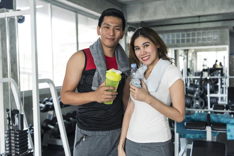 De jonge sportmensen houden fles, samen bekijkend camera en geglimlacht, in fitness gymnastiek stock afbeelding