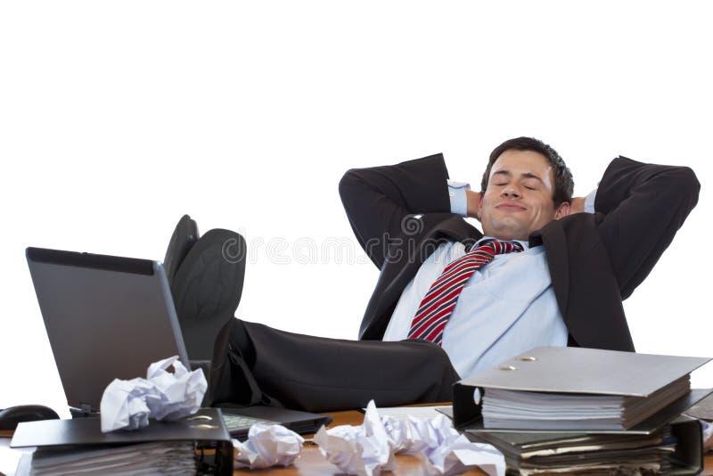 De jonge stafmedewerker ontspant met voeten bij bureau royalty-vrije stock afbeeldingen