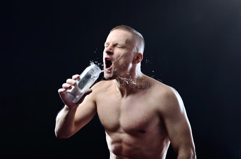 De jonge sterke atleet drinkt greedily water van een plastic fles op een donkere studioachtergrond royalty-vrije stock afbeelding