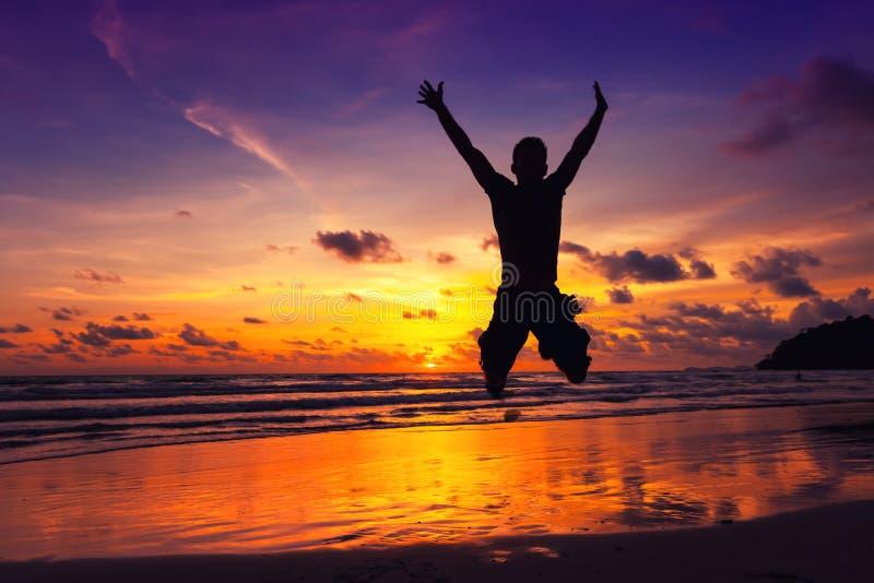 De jonge sterke mens geniet van vakantie op een tropisch eiland stock afbeelding