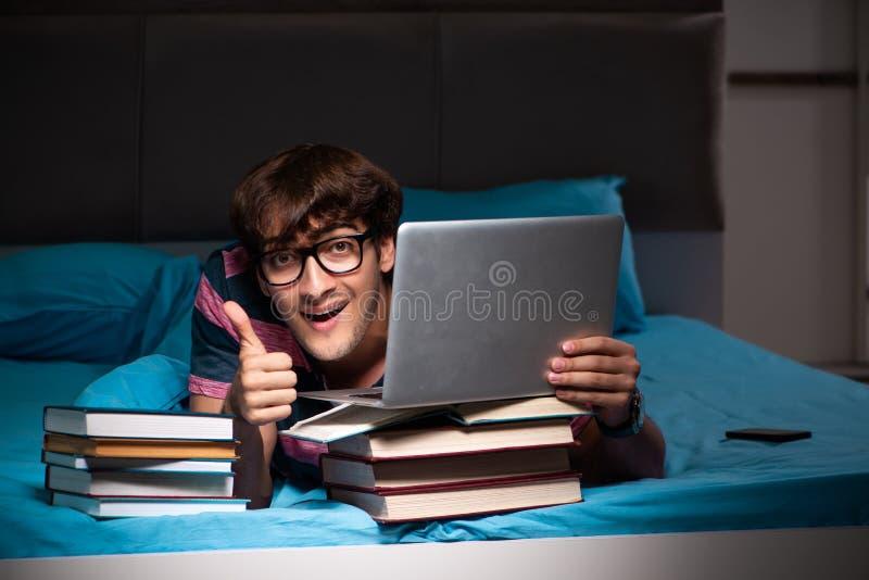 De jonge student die voor examens bij nacht thuis voorbereidingen treffen royalty-vrije stock foto