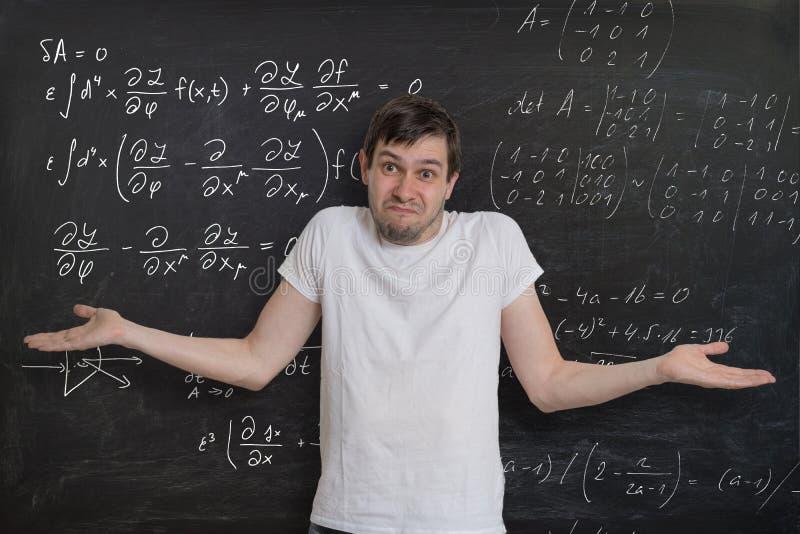 De jonge student doet wiskundeexamen en weet het hoe te om geen moeilijk wiskundig probleem op te lossen stock fotografie