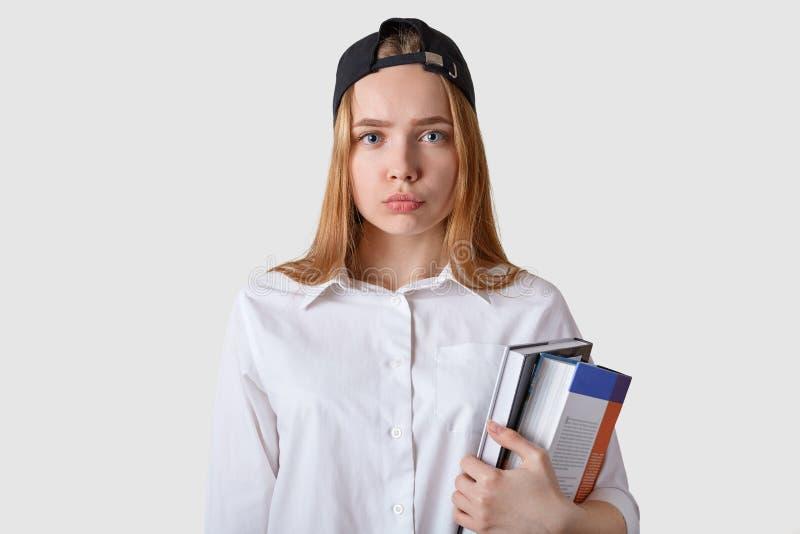 De jonge student heeft slecht resultaat van examen, die met ernstige en verstoorde gelaatsuitdrukking stellen Schoolmeisjetribune stock afbeelding