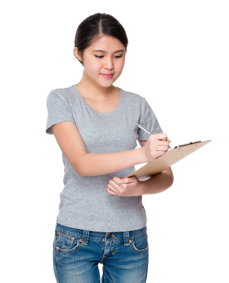 De jonge student noteert de informatie over klembord stock afbeelding
