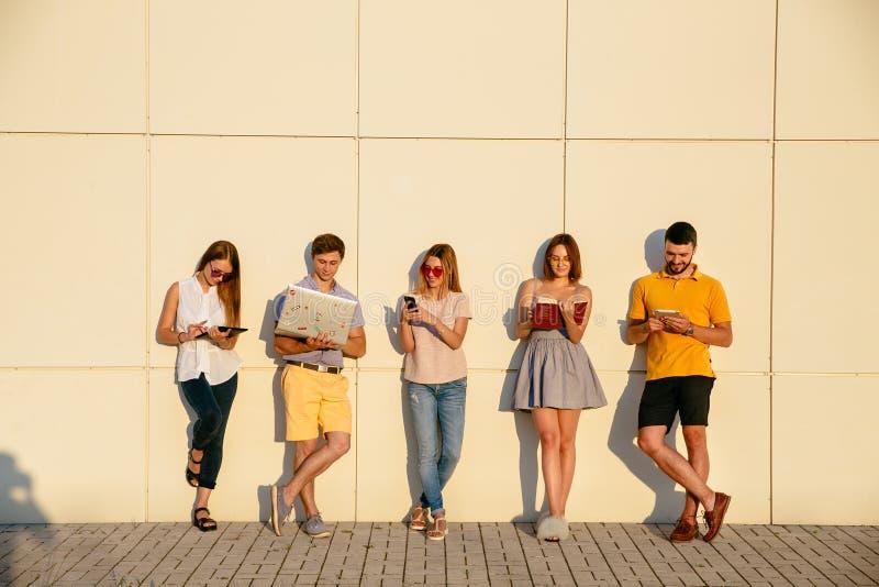 De jonge studenten gebruiken gadgets, het lezen van boek en glimlachen, die zich over muurachtergrond bevinden royalty-vrije stock foto
